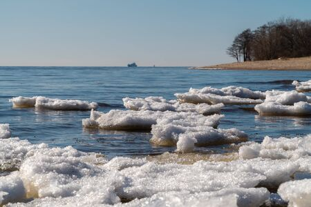 Russia. Saint-Petersburg. Remnants of ice and a view of the Gulf of Finland in early spring from the southern shore of Kronstadt.