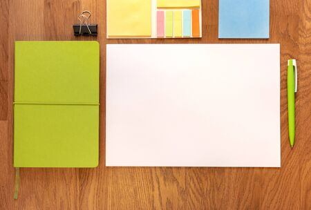 Paper, table, pen, notebook, stickers. White paper on the table. Notebook Template for message. Green style. remote office, remote work. Work place