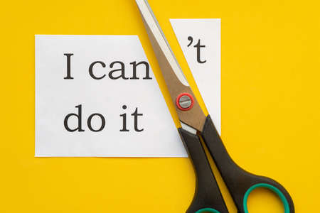 Paper with text I can't do it and scissors on yellow background