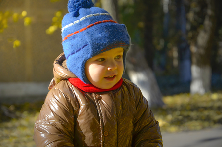 The kid in the autumn park in a blue hat and a brown jacket mysteriously looks away.