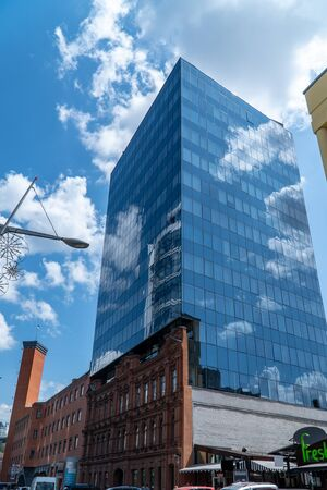 The front side of the old building is attached to it by the glass facade of the office building of the business center, which reflects the sky with clouds.
