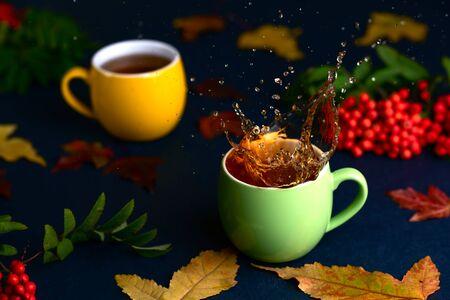 Autumn tea with rowan on blue handmade table