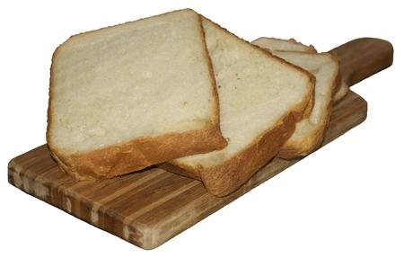 fresh wheat sliced bread on kichen board over white photo