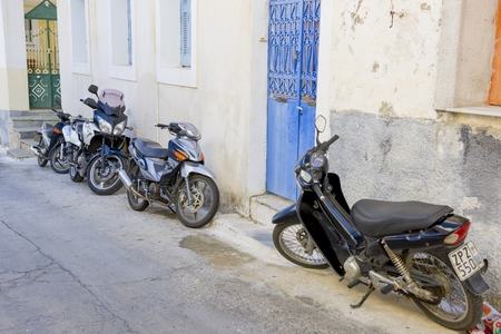 poros: Poros, Greece - September 27, 2014: Several modern scooters parked on old street in Poros island, Greece. Editorial