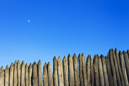 stockade: Palisade stockade palings logs and blue sky. Abstract background, old, ancient.