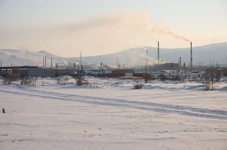 Industrial snowy landscape with mountain background photo