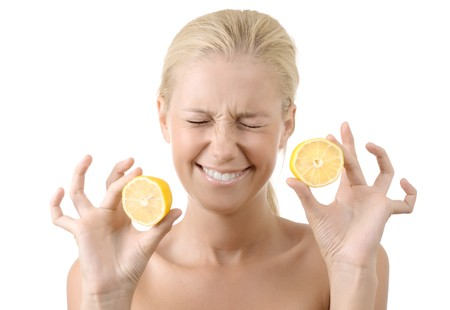 grimacing: Beautiful young girl holding a sour lemon isolated