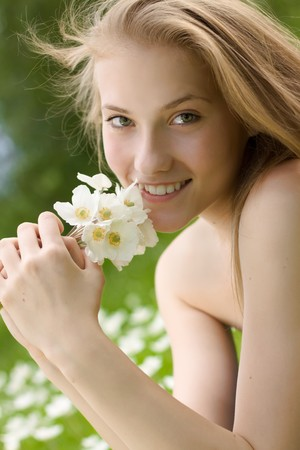 portrait of beautiful teen girl with white flowers in the park photo