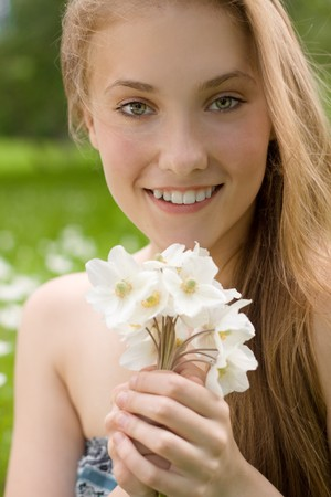 innocence: portrait of pretty teen girl with white flowers in the park