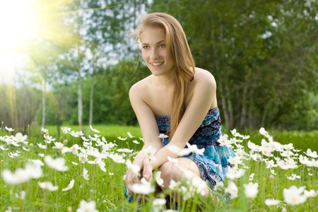 pretty teen girl on the field with snowdrops Stock Photo