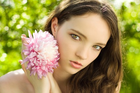 young teen girl nude: pretty teenager girl with flower on green background close-up Stock Photo