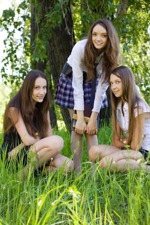 three beautiful student girls with books in the park photo