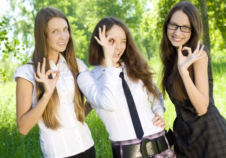 okey: three happy student girl give the sign okey in the park