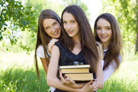 three happy student girl with books in the park photo