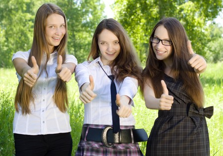 highschool: three happy student girl with thumbs-up in the park