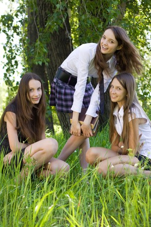 three pretty student girls with books outdoor photo