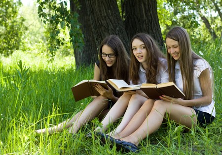 three students reading books together outdoor photo