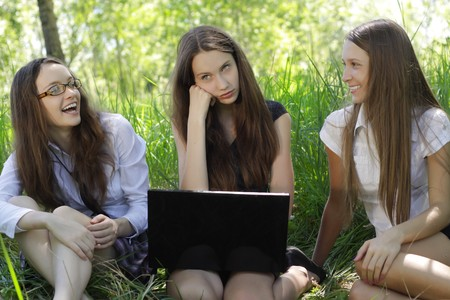 three students relax and laughing with notebook in the park   photo
