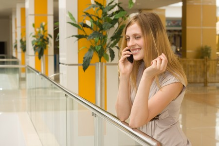 shopping centre: young attractive woman speaking on cellphone in shopping centre Stock Photo