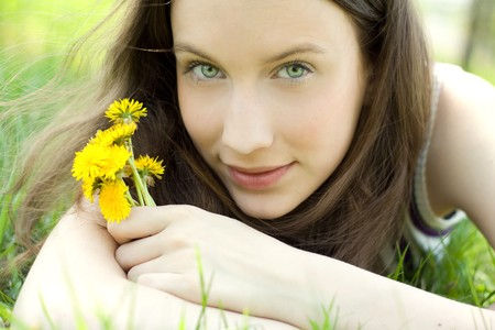 young beautiful teenager with dandelion bouquet photo