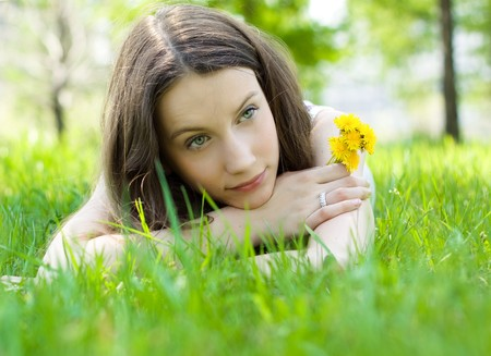 young beautiful teenager with dandelion on lawn photo