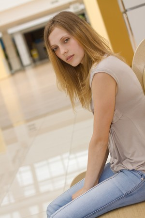 shopping centre: young woman sitting on the bench in the shopping centre Stock Photo