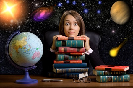 intellect: young woman with many books at the desk on space background Stock Photo