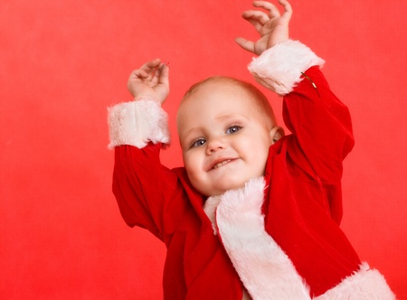 Happy baby boy in santa costume on red background photo
