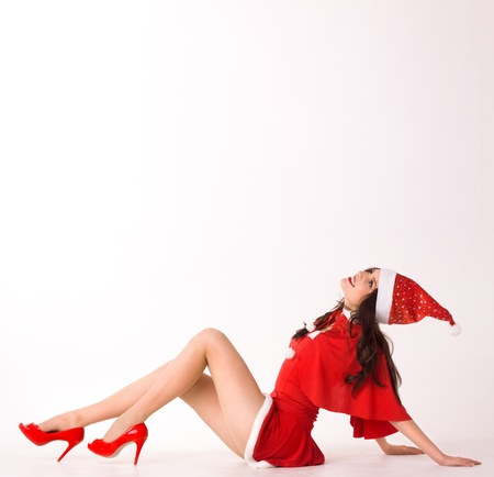 happy smiling woman in red xmas sexy costume lie and look up Stock Photo - 8380643