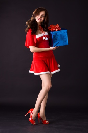 happy smiling woman in red xmas sexy costume with gift photo