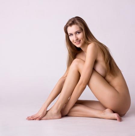 nudo di donna: Ritratto di sana sorridente donna nuda su sfondo grigio