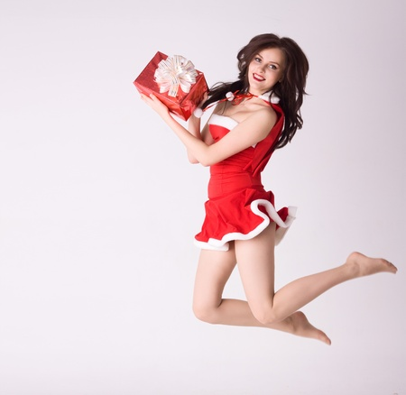 smiling woman in red xmas sexy costume fly with gift photo