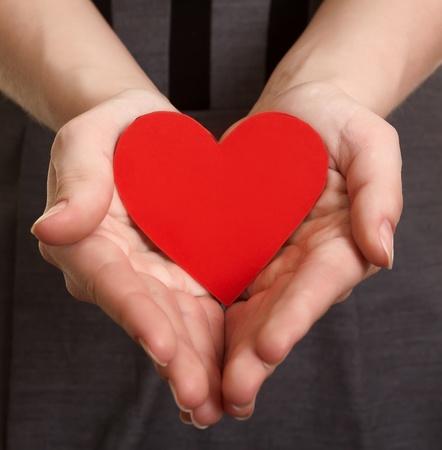 corazon en la mano: coraz�n de papel rojo en las manos Foto de archivo