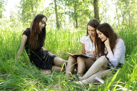 three students reading books in park photo
