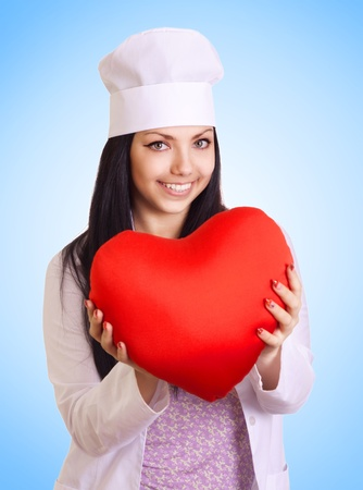 Female doctor holding heart on blue background photo