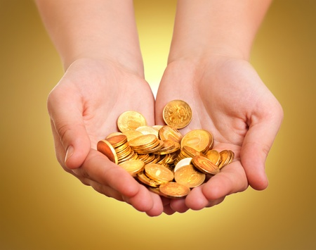 Hands with gold coins on yellow background  photo