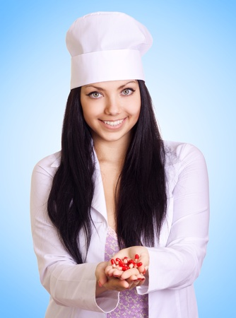 chearful: young medical doctor with red pills in hands on blue background  Stock Photo