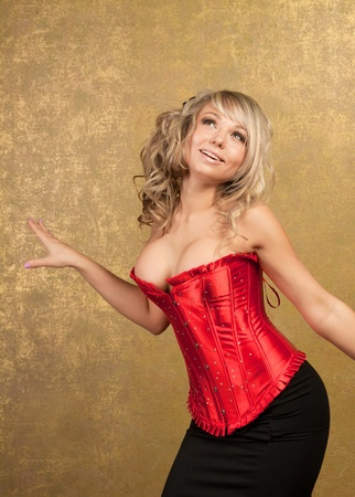 red corset: sexy blonde woman in red corset and skirt on golden background