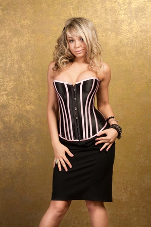 sexy blonde woman in corset and skirt on golden background photo