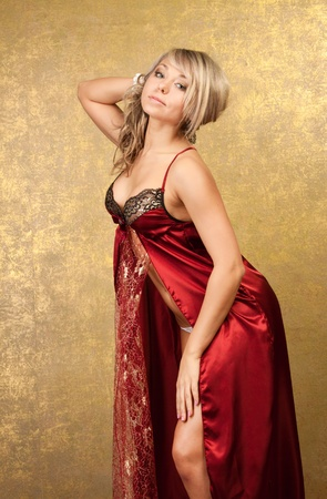 sexy blonde woman in red seductive dress on golden background Stock Photo - 9418722
