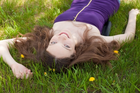 young beautiful teenager on dandelion lawn