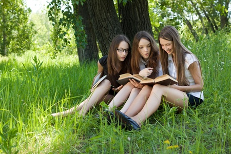 three students reading books together outdoor  Stock Photo - 9617507