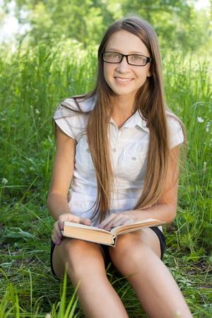 school teens: chica joven estudiante sentado en el parque con libro Foto de archivo