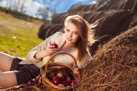 beautiful blonde smiling woman with many apple in basket on haystack at farm  Stock Photo - 9615417