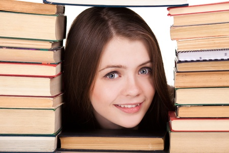 Teen girl with lot of books around, isolated on white  photo