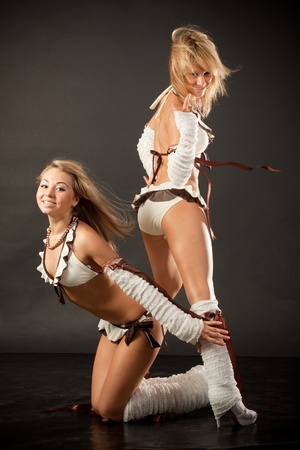 two beautiful dancer girl in white costumes on black background photo