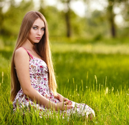 beautiful young blonde woman on the meadow on a warm summer day  photo