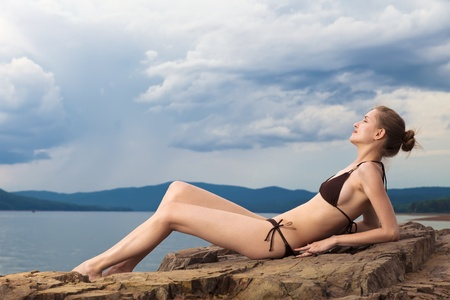 Beautiful happy woman sitting on rock over sea at summer storm day  photo
