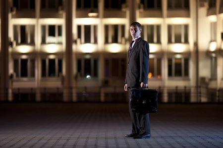 Handsome businessman with briefcase at night city in the background  photo