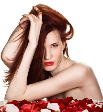 labios rojos: Hermosa mujer y p�talos de rosa sobre fondo blanco  Foto de archivo